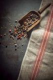 Granelli di pepe misti secchi che straripano un mestolo Fotografia Stock