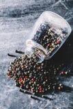 Granelli di pepe secchi variopinti rovesciati e un barattolo di vetro trasparente Fotografia Stock
