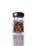 Granello di pepe colorato barattolo su fondo bianco Fotografia Stock Libera da Diritti