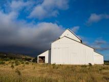 Granero blanco debajo de Grey Clouds Imagen de archivo libre de regalías