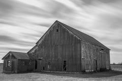 Granero blanco y negro rústico viejo con el movimiento de la nube foto de archivo libre de regalías