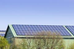 Granero con los paneles solares en el tejado y el cielo azul Imagen de archivo libre de regalías