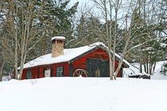 Granero de madera rojo rústico en nieve Imagenes de archivo