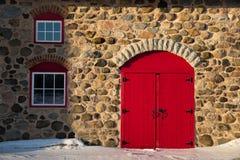 Granero de piedra viejo con la puerta roja brillante Imágenes de archivo libres de regalías