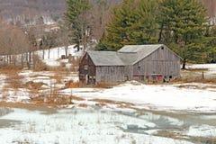 Granero en nieve con helado sobre los charcos en el norte del estado NY Fotografía de archivo