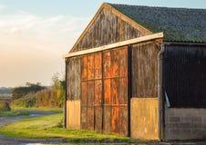 Granero en tierras de labrantío con las puertas rojas y oxidadas del metal Imagen de archivo