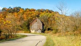 Granero rústico de Brown en medio de árboles coloreados caída imágenes de archivo libres de regalías