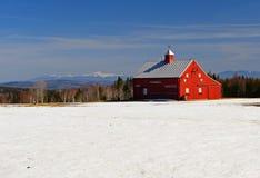 Granero rojo brillante y campo nevado Fotos de archivo libres de regalías