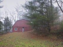 Granero rojo en niebla del invierno Foto de archivo
