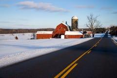 Granero rojo a lo largo del camino en invierno Imagenes de archivo