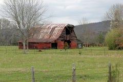 Granero rojo que se sienta en campo delante de las montañas Foto de archivo libre de regalías