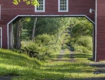 Granero rojo viejo con el camino de tierra que corre a través de él Imagen de archivo libre de regalías