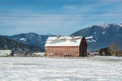 Granero rojo viejo en fondo mountaing de la visión Fotografía de archivo