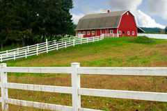 Granero rojo y cerca blanca Fotografía de archivo libre de regalías