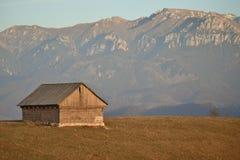 Granero tradicional viejo del heno en el área de montaña con un fondo una cordillera Foto de archivo