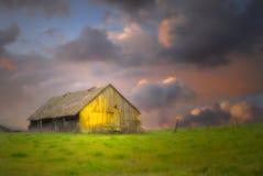 Granero viejo bajo los cielos oscuros con el foco suave Imagenes de archivo