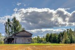 Granero viejo con el cielo azul y las nubes Imágenes de archivo libres de regalías