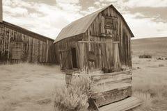 Granero viejo del exterior bien en Bodie, California en sepia Fotos de archivo libres de regalías