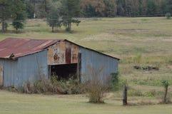 Granero viejo del metal del abandono en campo Foto de archivo libre de regalías