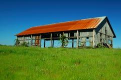 Granero viejo en campo de hierba fotografía de archivo