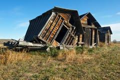 Graneros de madera abandonados en campo herboso imagen de archivo