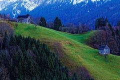 Graneros en paisaje alpino por crepúsculo Imagen de archivo libre de regalías
