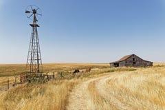 Graneros, establos y molino de viento de madera en el campo de Dakota del Norte foto de archivo