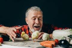 Granfather émotif ayant l'amusement avec des poulets sur la table photo stock
