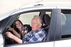 Granfather, nieto y perro en coche Imagen de archivo libre de regalías