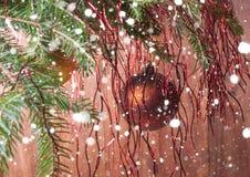 Granfilialer med julbollar Stylized fallande snö Arkivfoto