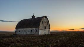 Grange abandonnée au coucher du soleil Photos stock