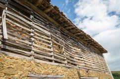 Grange avec la paille enregistrée derrière une frontière de sécurité en bois Photographie stock libre de droits