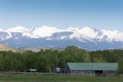 Grange contre les montagnes rocailleuses photographie stock libre de droits