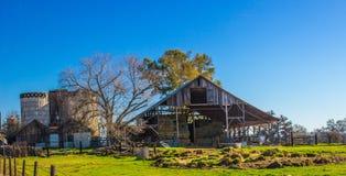 Grange d'air ouvert avec des silos contre le ciel bleu Photo libre de droits