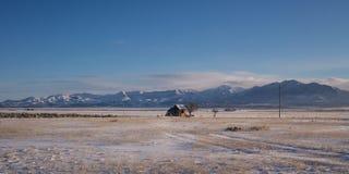 Grange dans un domaine de neige ouvert Image libre de droits