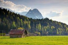 Grange en bois dans le pré vert avec le massif de domination de Zugspitze image libre de droits