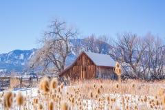 Grange en bois dans un espace ouvert couvert de neige Image stock