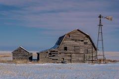 Grange, poubelles et moulin à vent de cru entourés par la neige sous un ciel rose de coucher du soleil en Saskatchewan image stock
