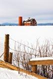 Grange rouge dans la neige avec une barrière rustique Photographie stock