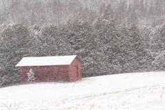 Grange rouge dans la tempête de neige de neige Photographie stock libre de droits