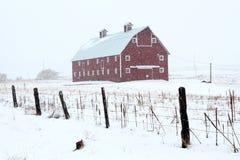 Grange rouge en tempête de l'hiver Photographie stock libre de droits