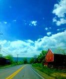 Grange rouge le long d'une route de campagne Image libre de droits