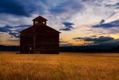 Grange silhouettée au coucher du soleil Images libres de droits
