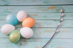 Red, multicolor, orange and green easter eggs on the blue wooden background stock photo
