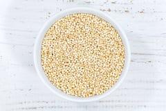 Grani del superfood dei superfoods del grano della quinoa da sopra la ciotola di legno fotografia stock libera da diritti