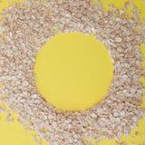 Grani della farina d'avena su fondo giallo, spazio della copia I fiocchi di avena si trovano sotto forma di cerchio immagini stock libere da diritti