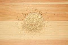 Grani della quinoa su legno fotografia stock