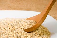 Grani della quinoa su un primo piano del bordo di legno fotografia stock libera da diritti