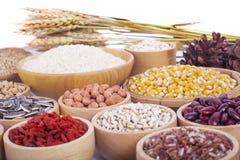 Grani di cereali, semi, fagioli su fondo di legno immagini stock libere da diritti