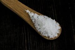 Grani di sale su un cucchiaio di legno Fotografia Stock Libera da Diritti